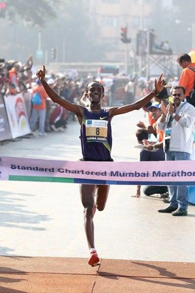 Girma Assefa smiles as he breaks the tape in Mumbai. Photo: IAAF