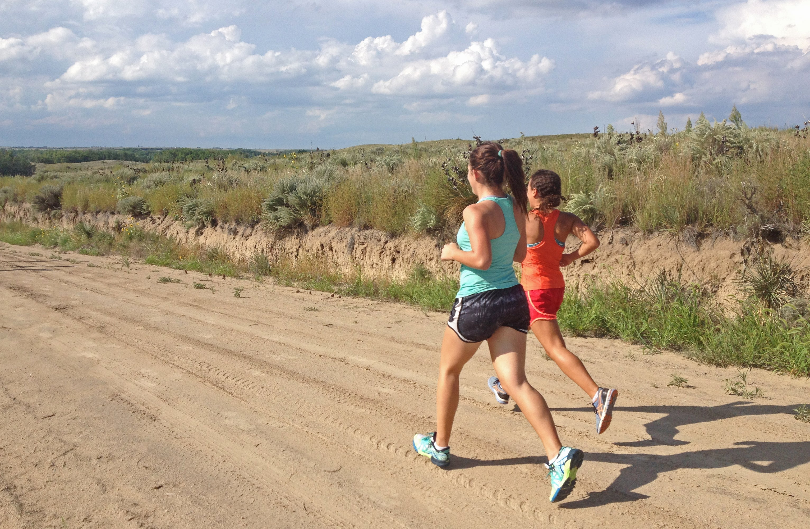 young women runners tempo dirt road