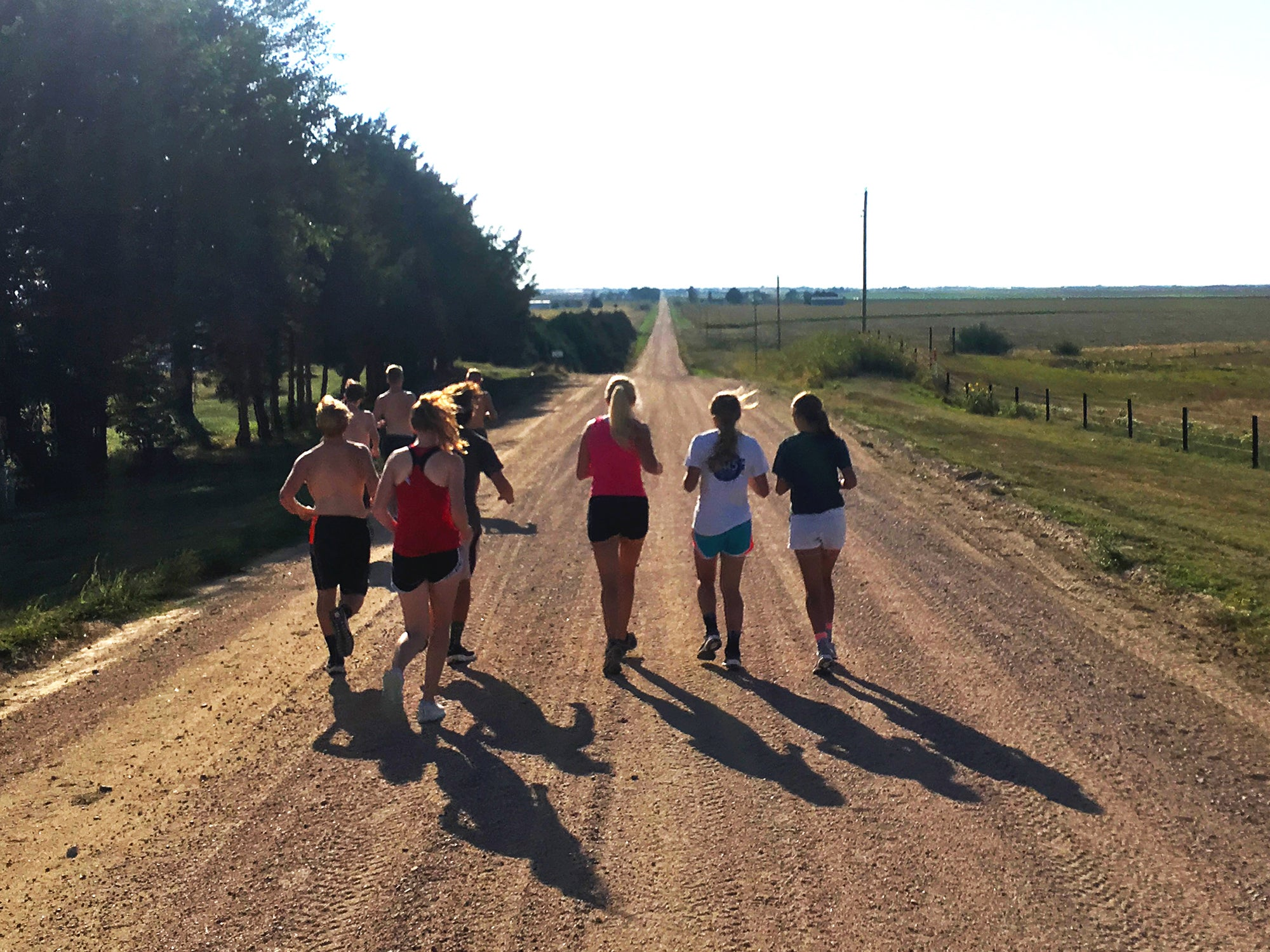 group of young runners hot day dirt road