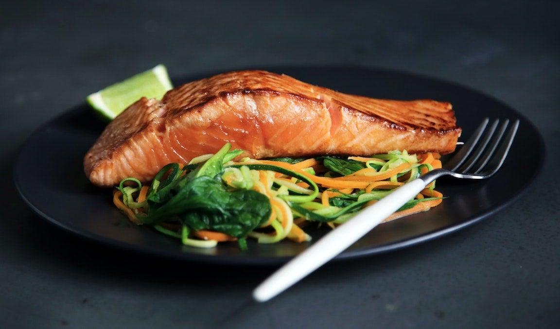 Trozo de salmón (a la plancha) sobre un lecho de verduras.