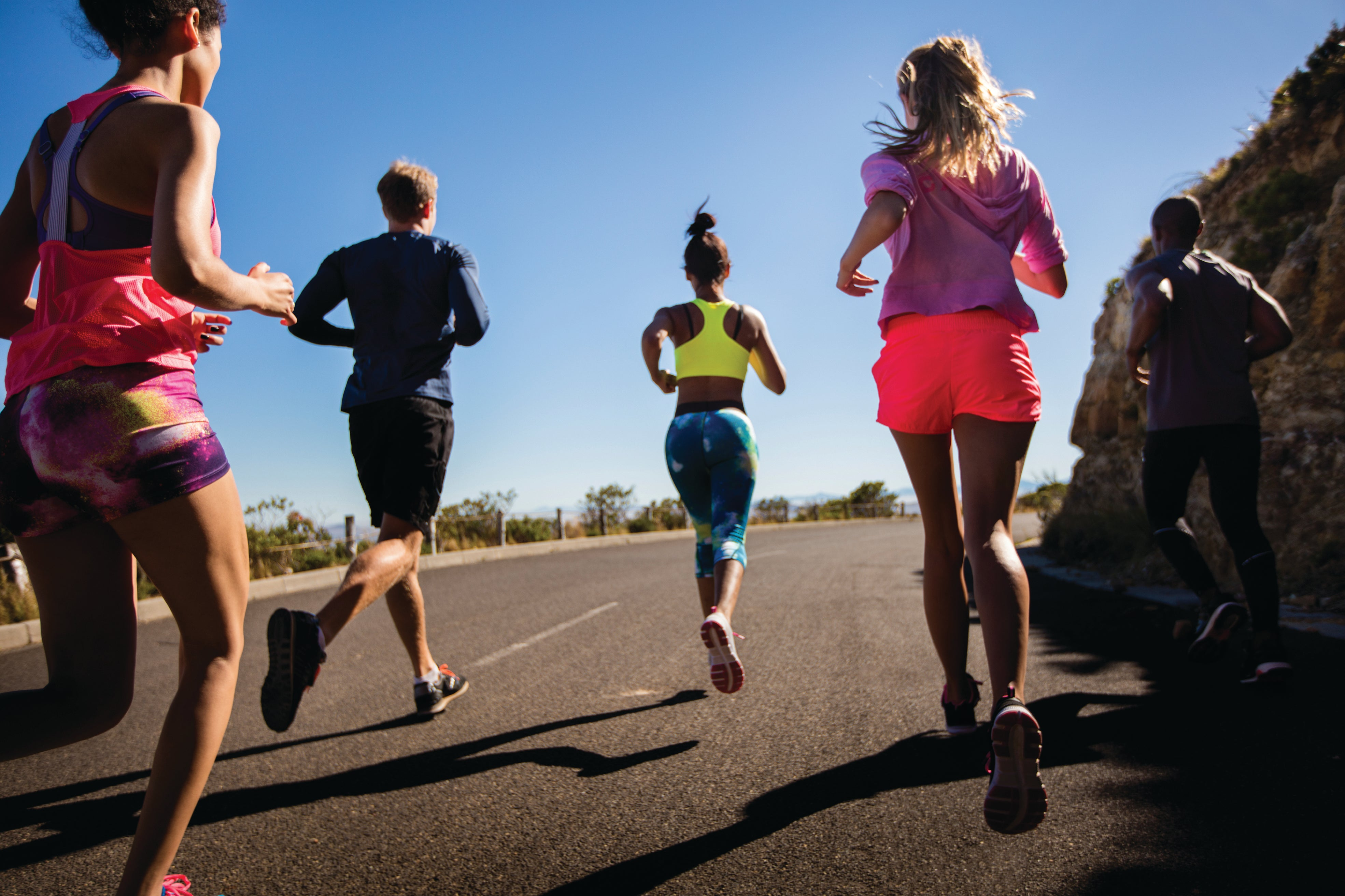 Group of athletes running outdoors in summer