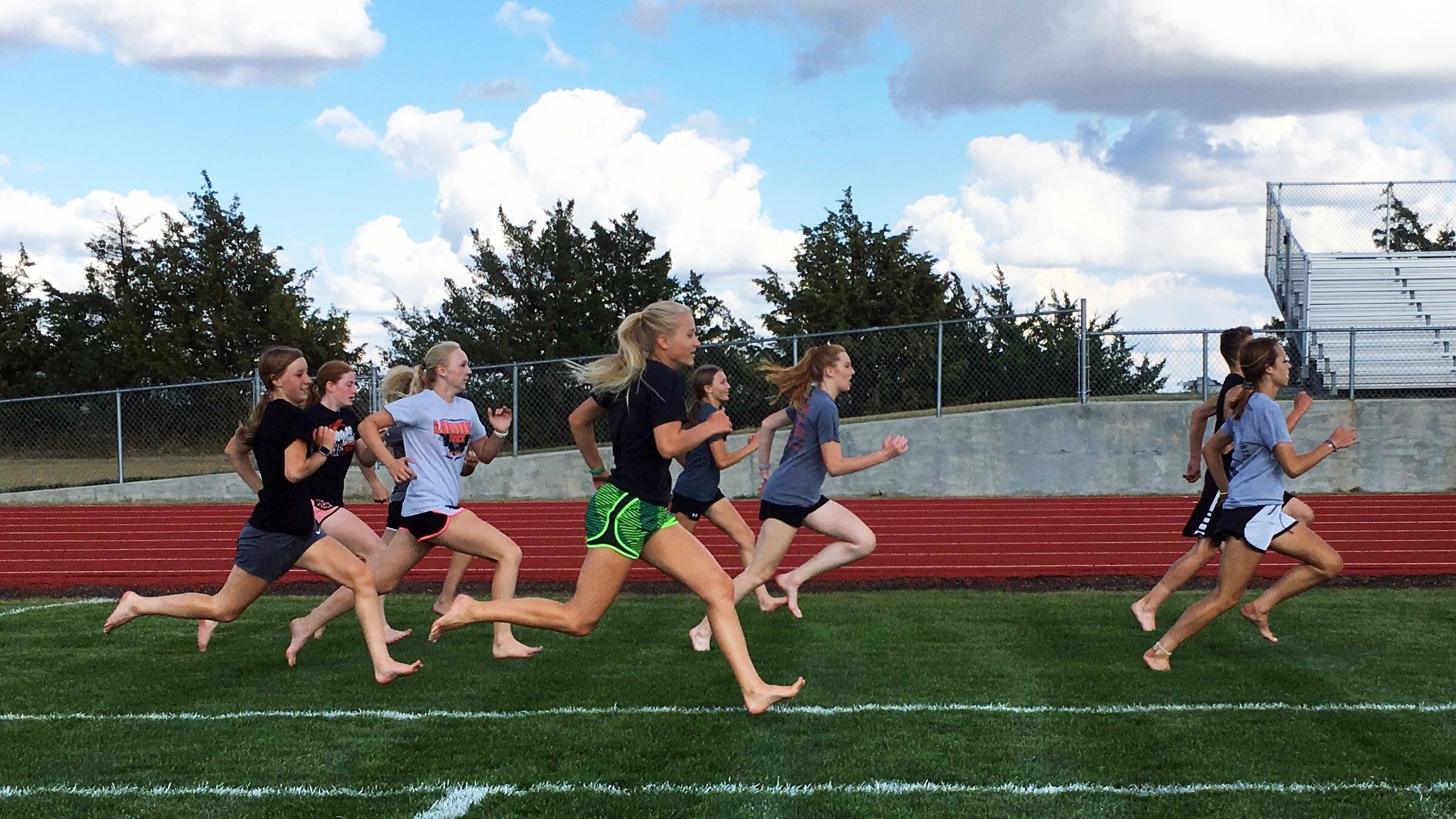 female runners doing barefoot strides on grass