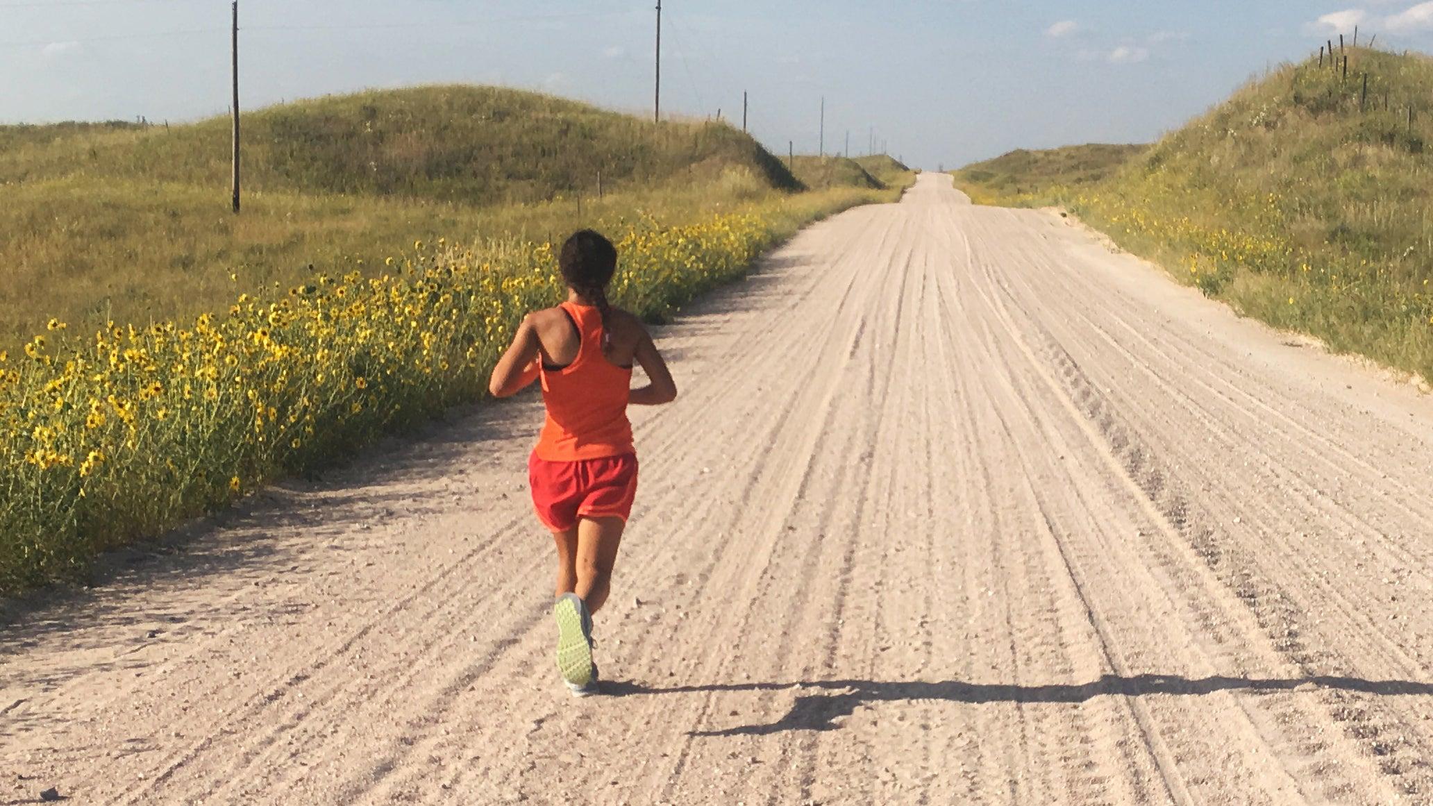 woman running long dirt road