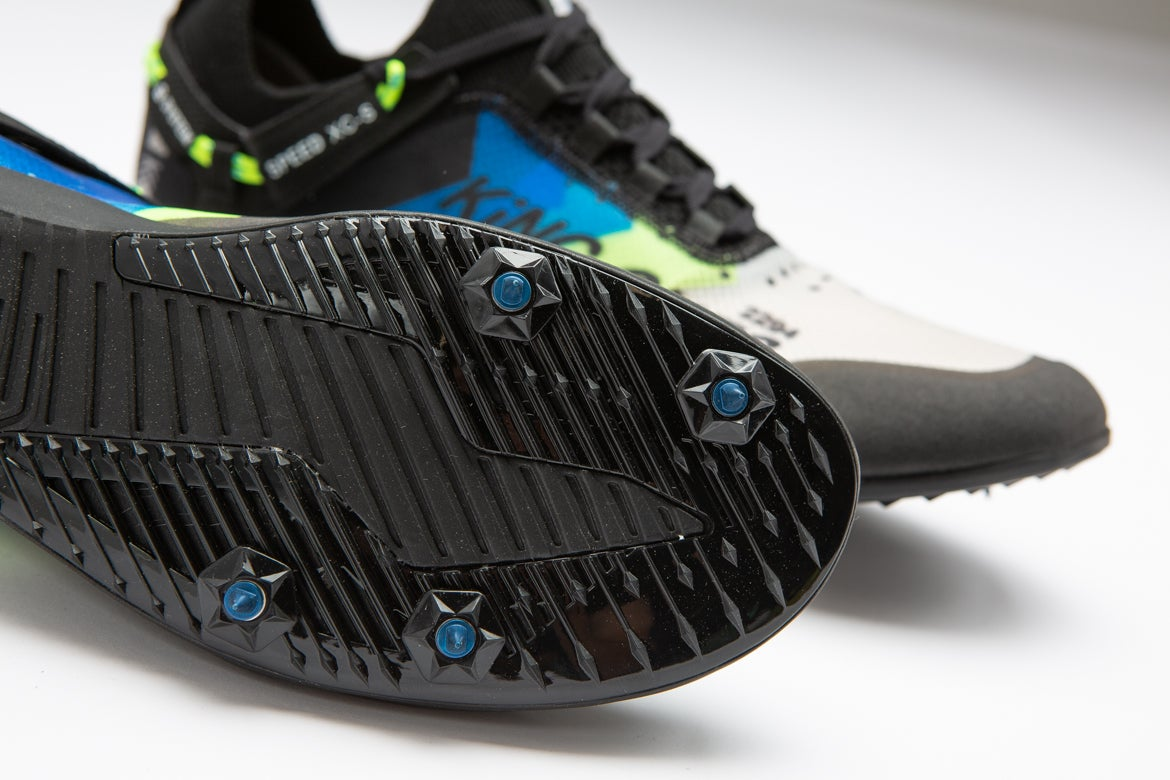 Skechers xc5 cross country running spike in profile. black, blue, and white. Showing bottom of shoe with spikes.
