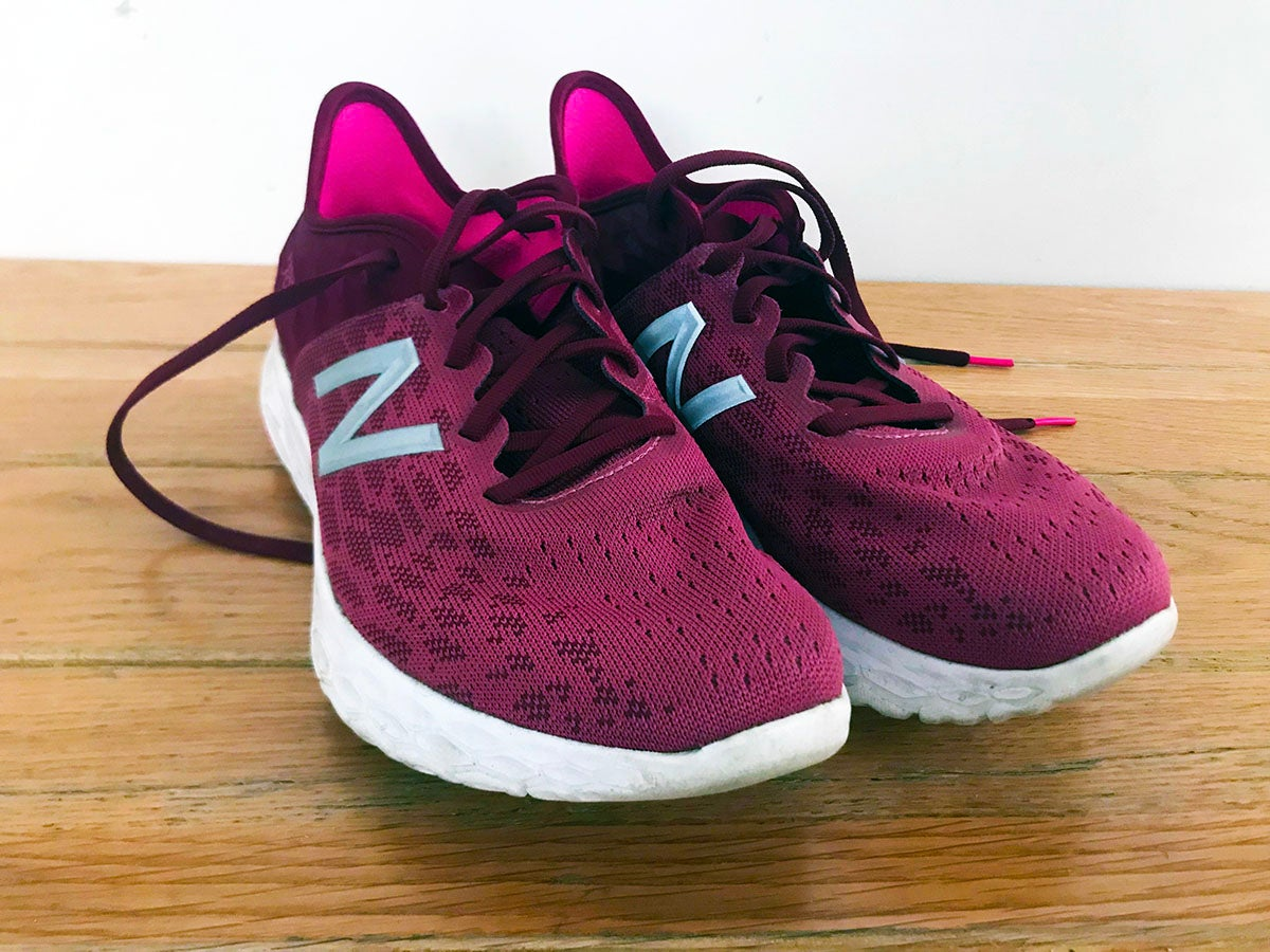 magenta new balance fresh foam v2 running shoes feature shot on a wooden floor with white background