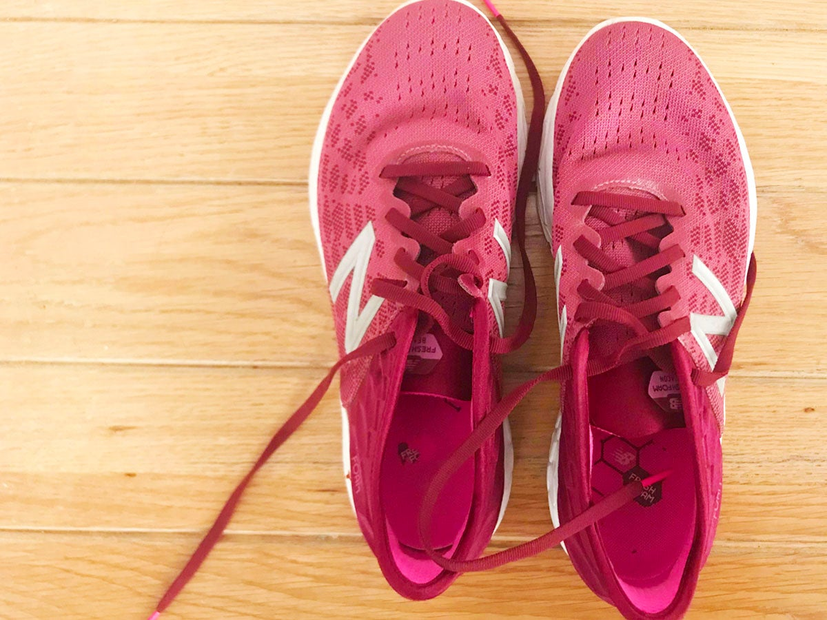 magenta road running shoes with laces made by New Balance on a wooden floor background