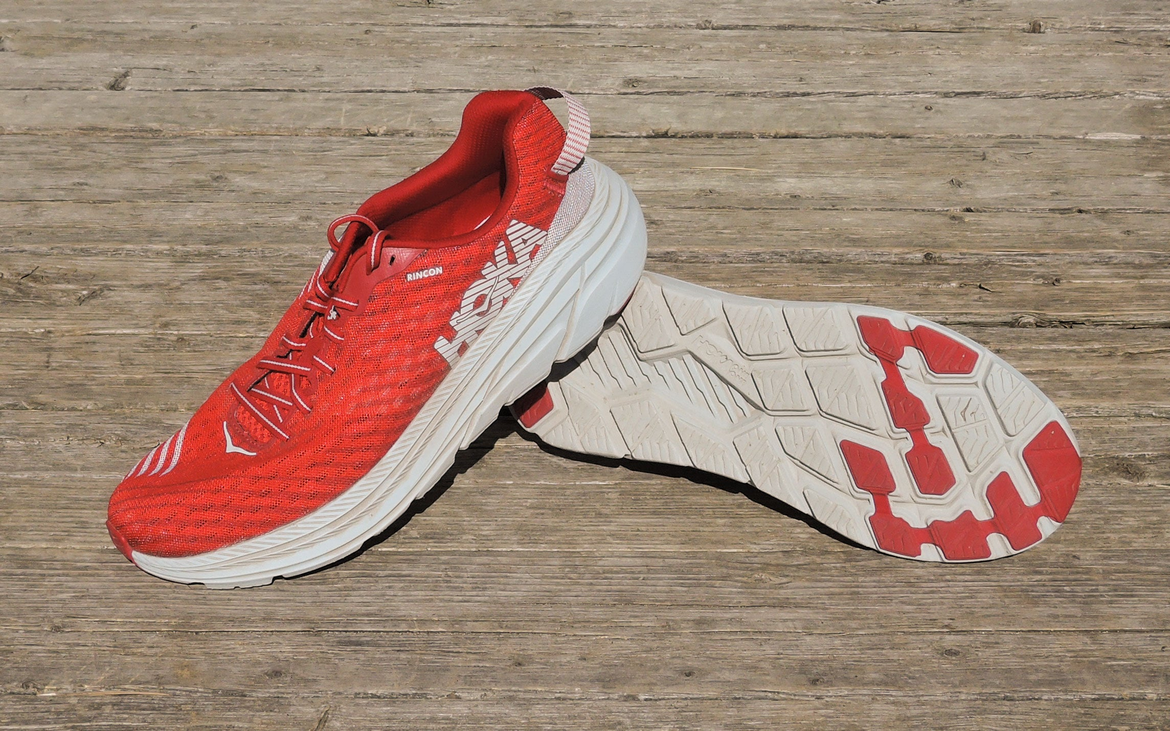 HOKA rincon running shoes for trails on a wood background in pink, red and white
