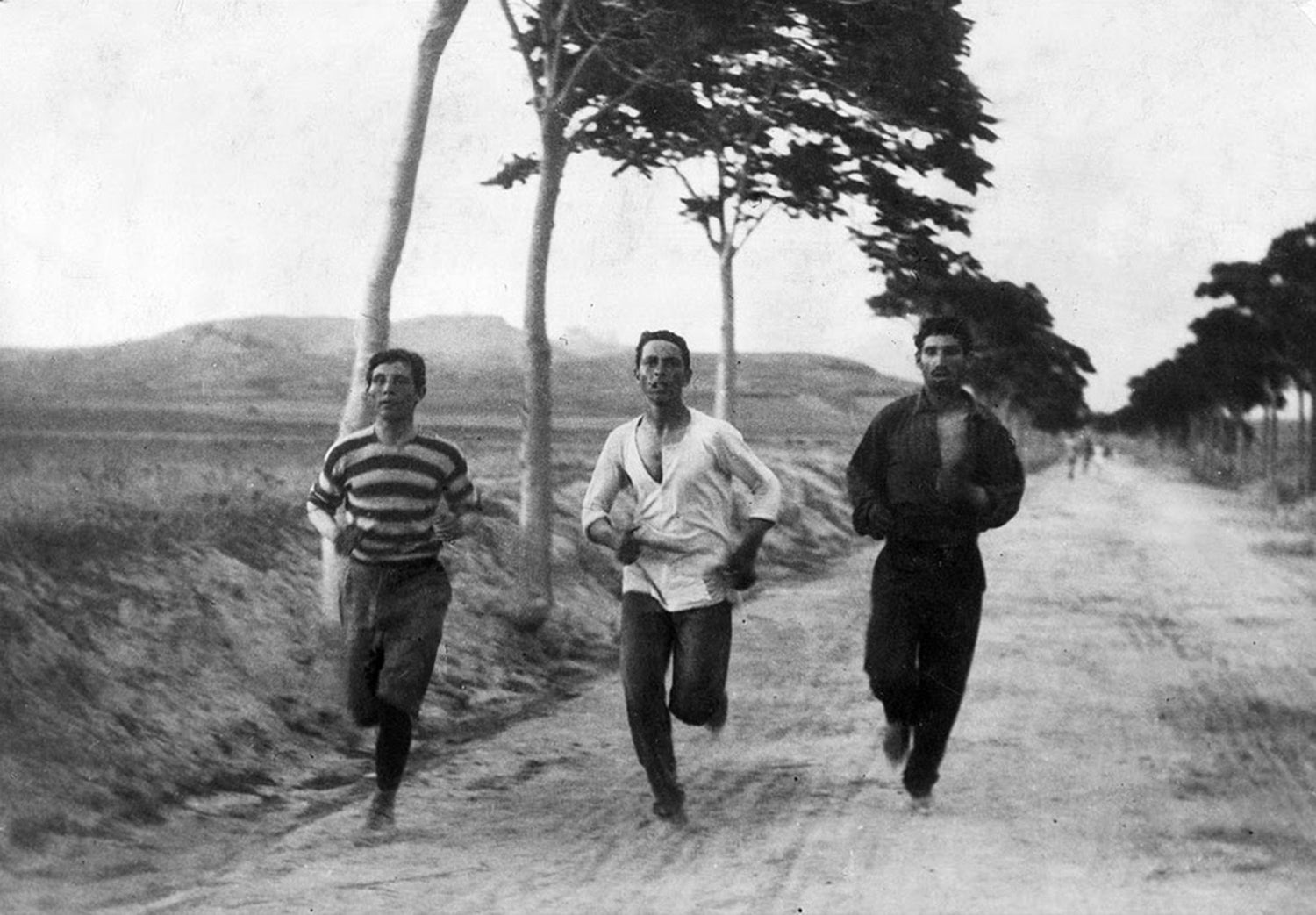 Three athletes in training for the marathon race of the 1896 Athens Olympic Games, on the road from Marathon, Greece, Vasilakos in the middle.