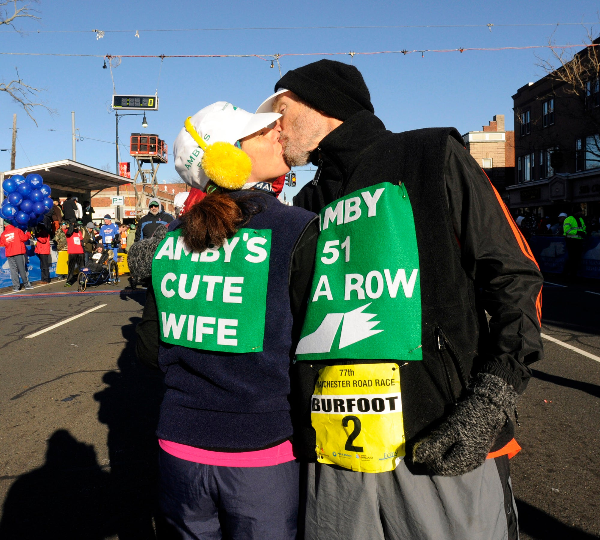 Amby Burfoot gets a kiss from his wife Cristina as he prepares for his 51 st Manchester Road Race in a row in 2013, setting the all time record.