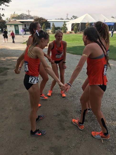 Oregon State University runners laughing in a circle.