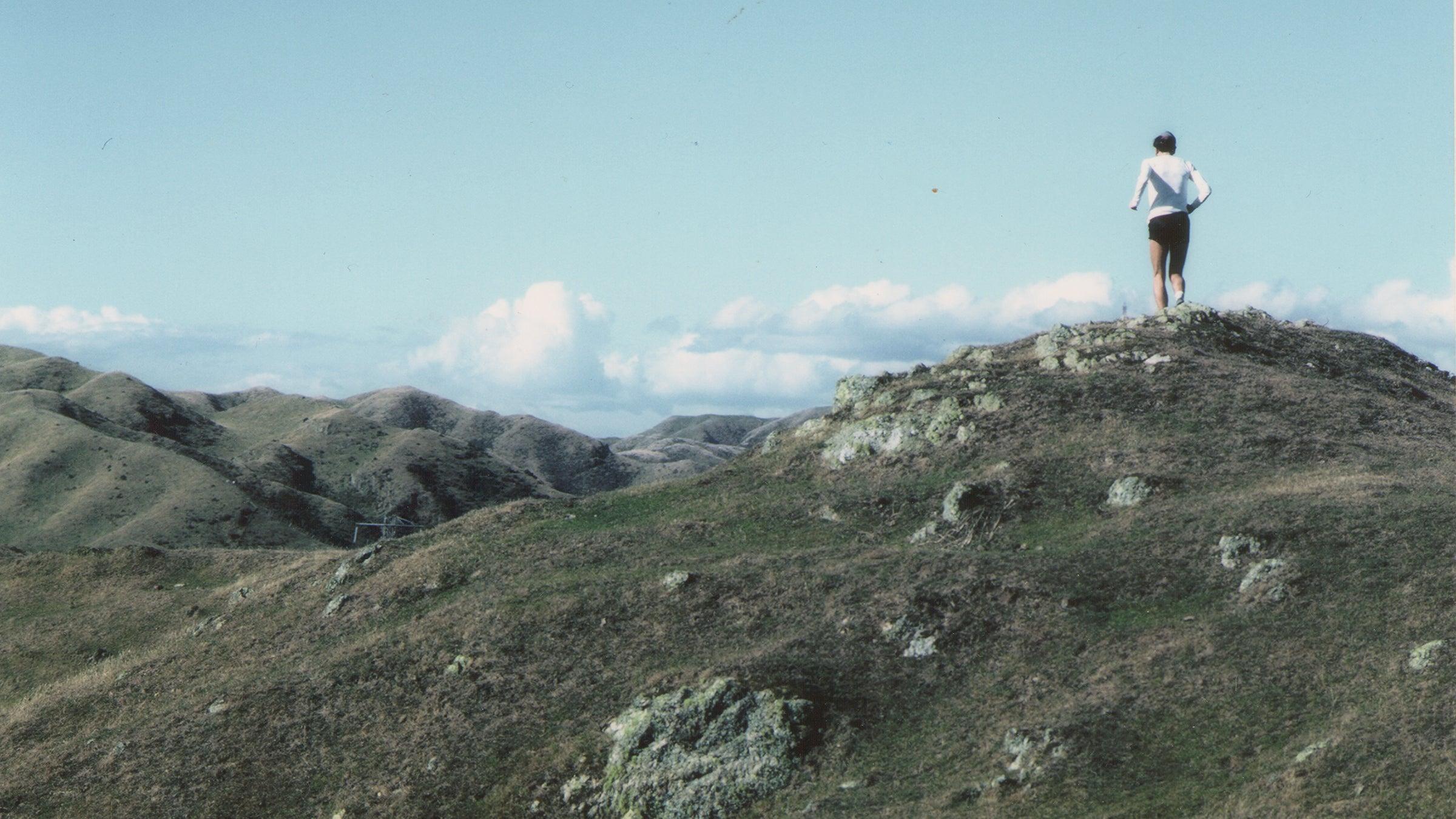 runner on peak of rolling hills