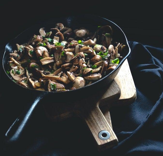 Mushrooms being cooked in pan.