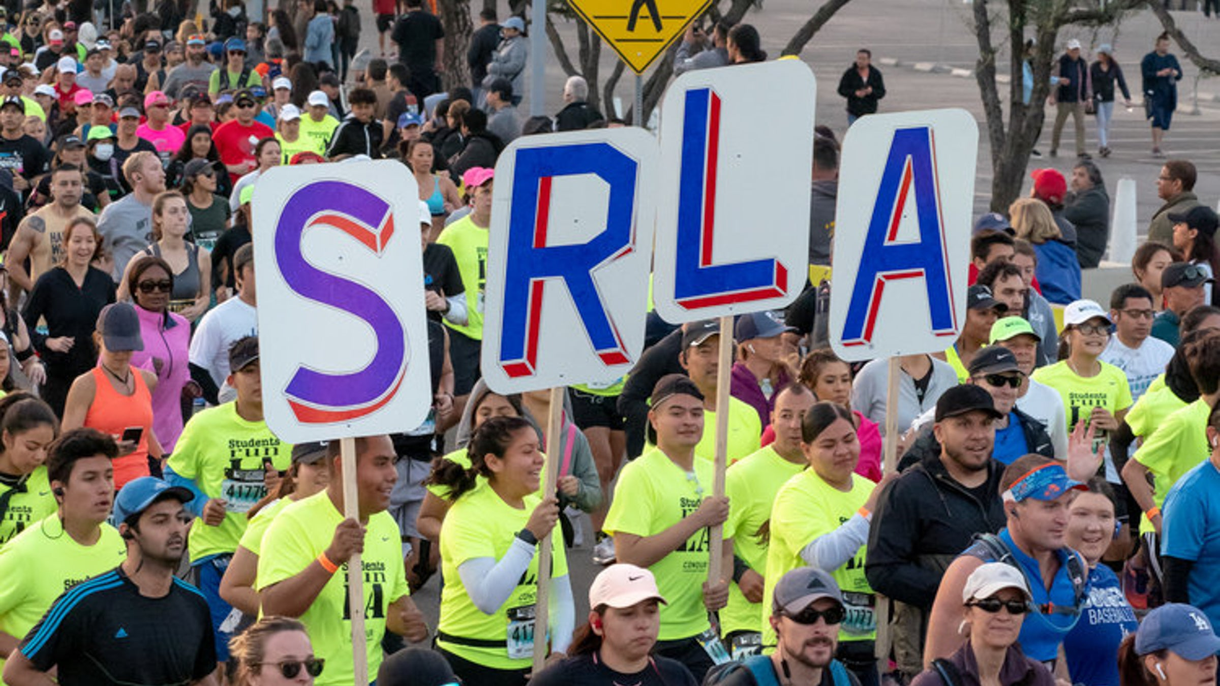 Close-up of SRLA members holding signs that spell SRLA