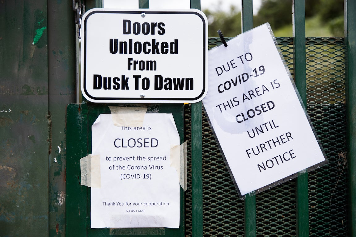 """Several signs posted to a gate say """"Doors unlocked from dusk to dawn,"""" """"This area is CLOSED to prevent the spread of corona virus,"""" and """"Due to COVID-19 this area is CLOSED until further notice"""""""