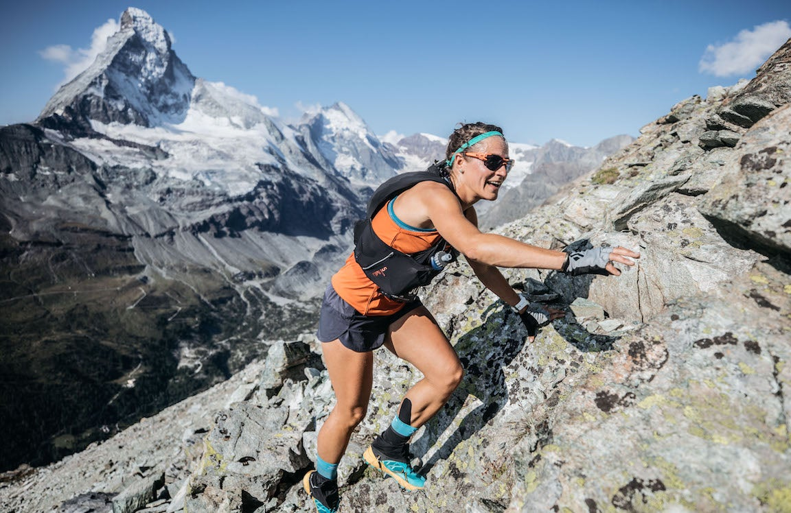 Woman climbing up steep rocky mountain face with mountains in background