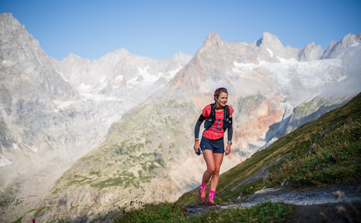 Woman hiking on trail with mountains in background