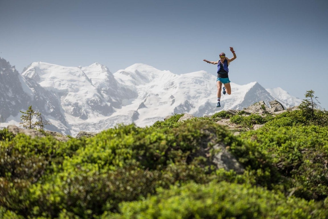 Female trail runner jumping over obstacle with snowy mountains in background