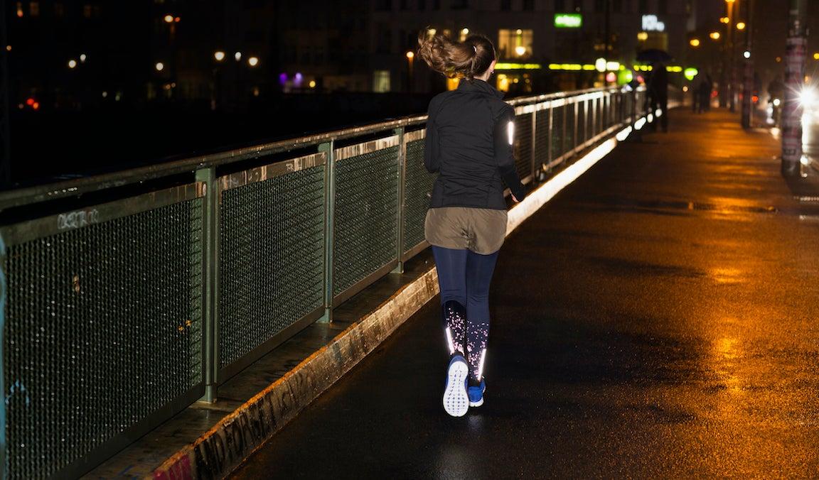 Woman jogging along a wet sidewalk in an urban area at night