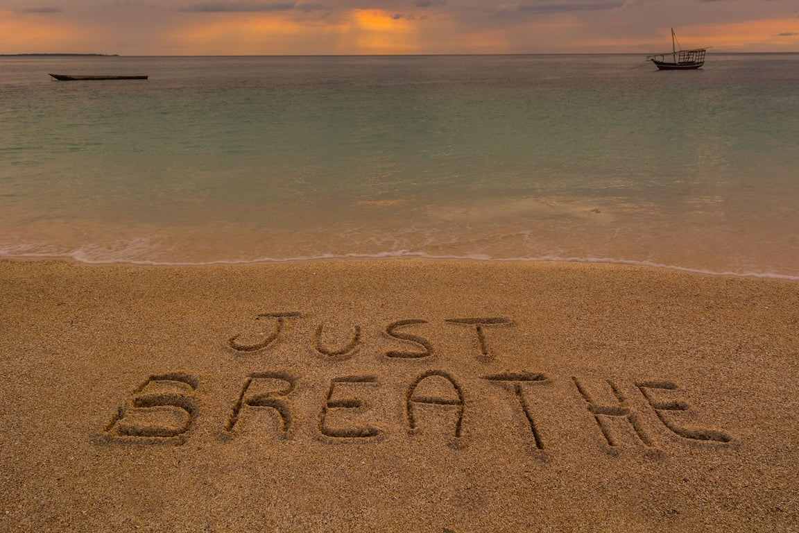 """Just breathe"" words in sand."