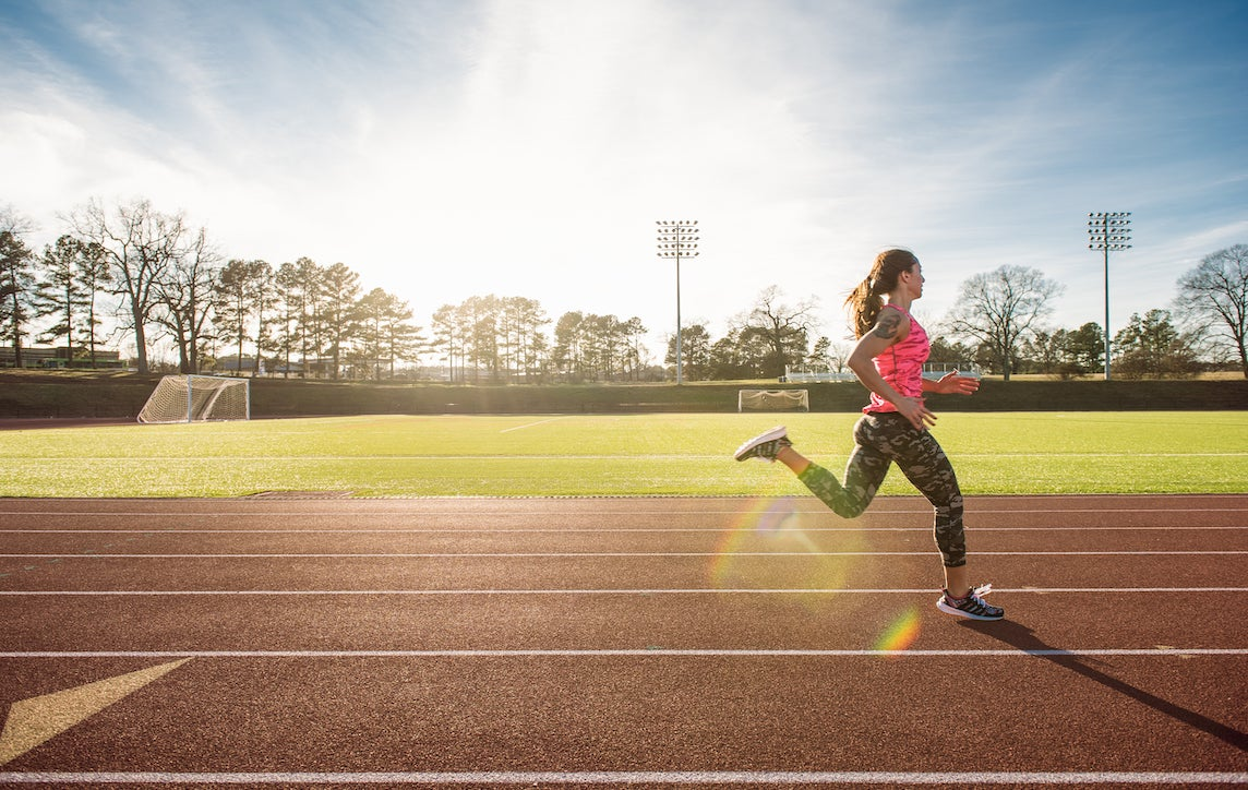 Young female athlete running on race track
