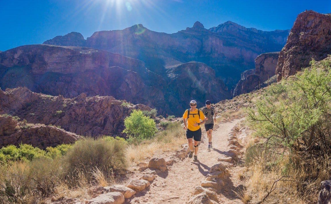 Two men running along a trail with a sunny canyon in the background