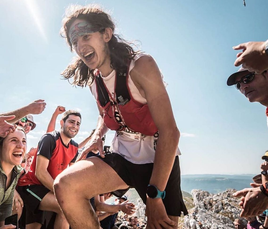 Ultrarunner surrounded by cheering people summiting a mountain on a sunny day