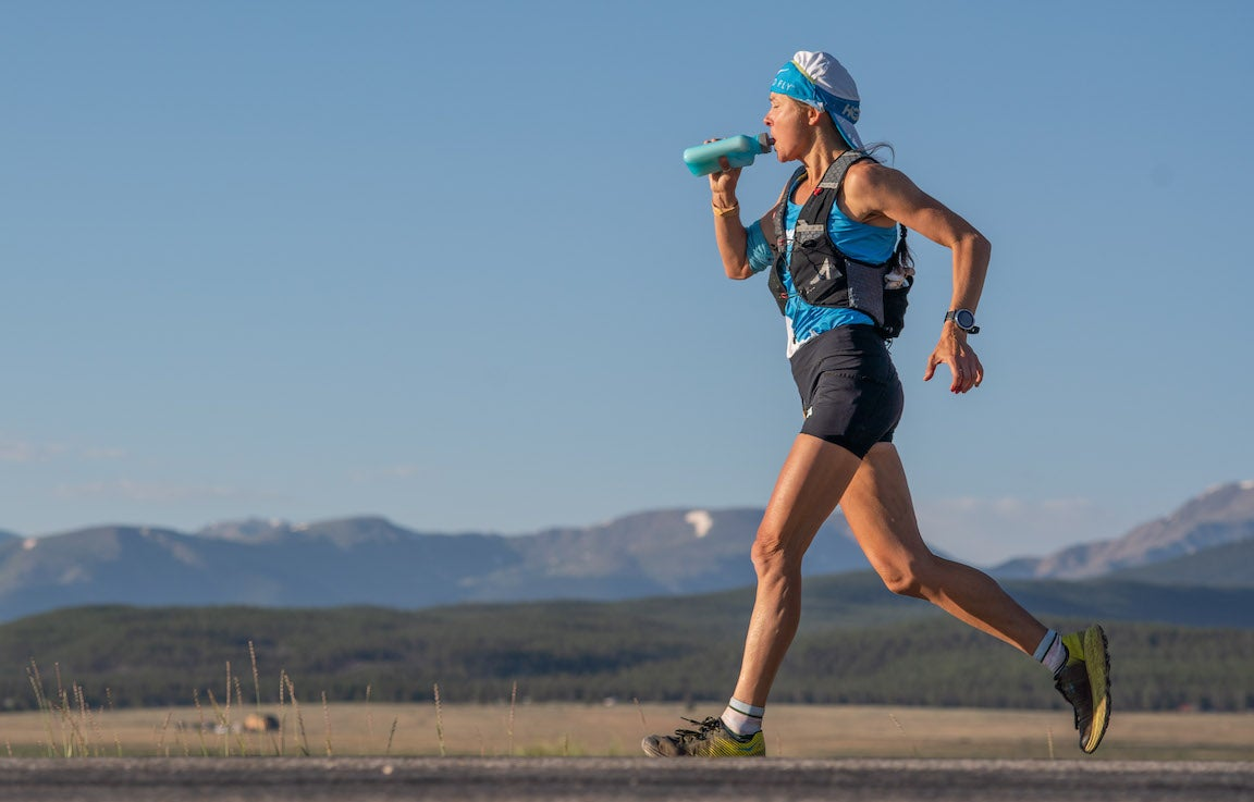 Woman running and drinking from water bottle.