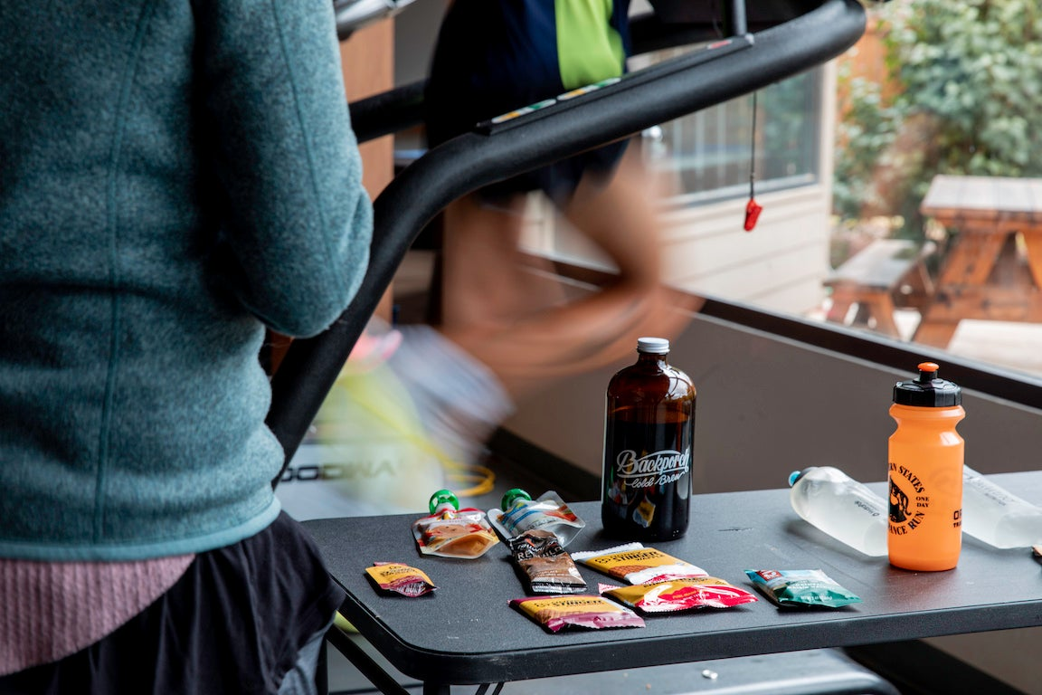 cold brew coffee on table while man runs on treadmill
