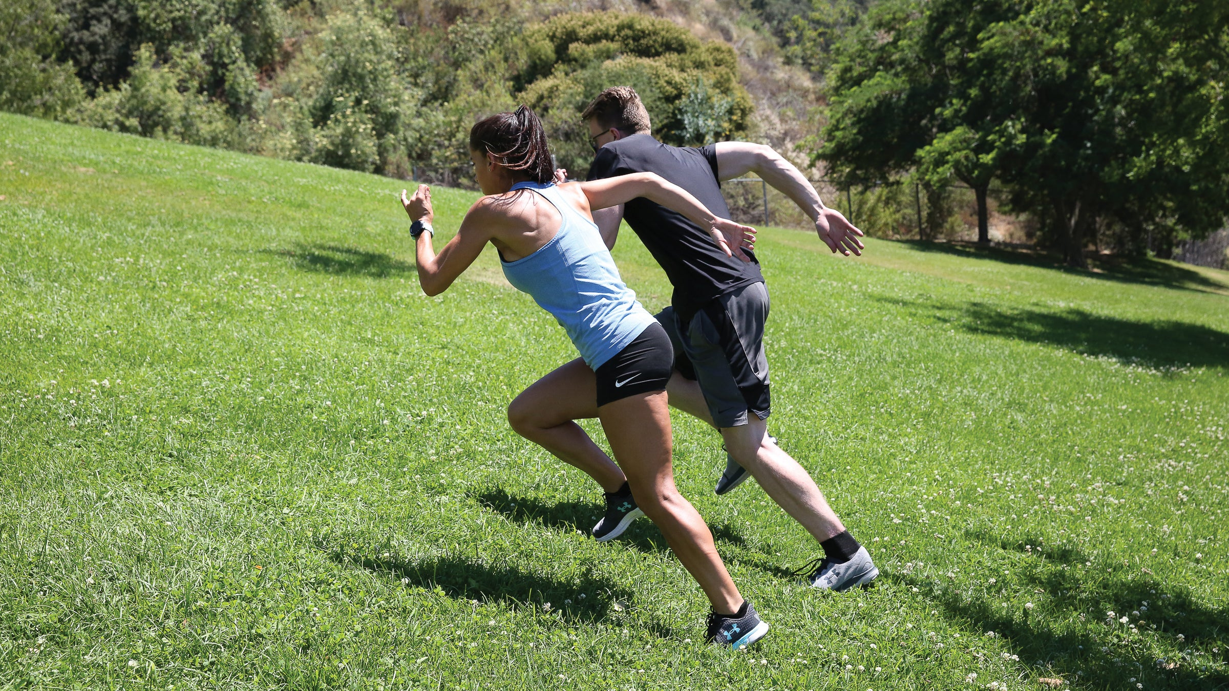 Man and woman performing hill sprints