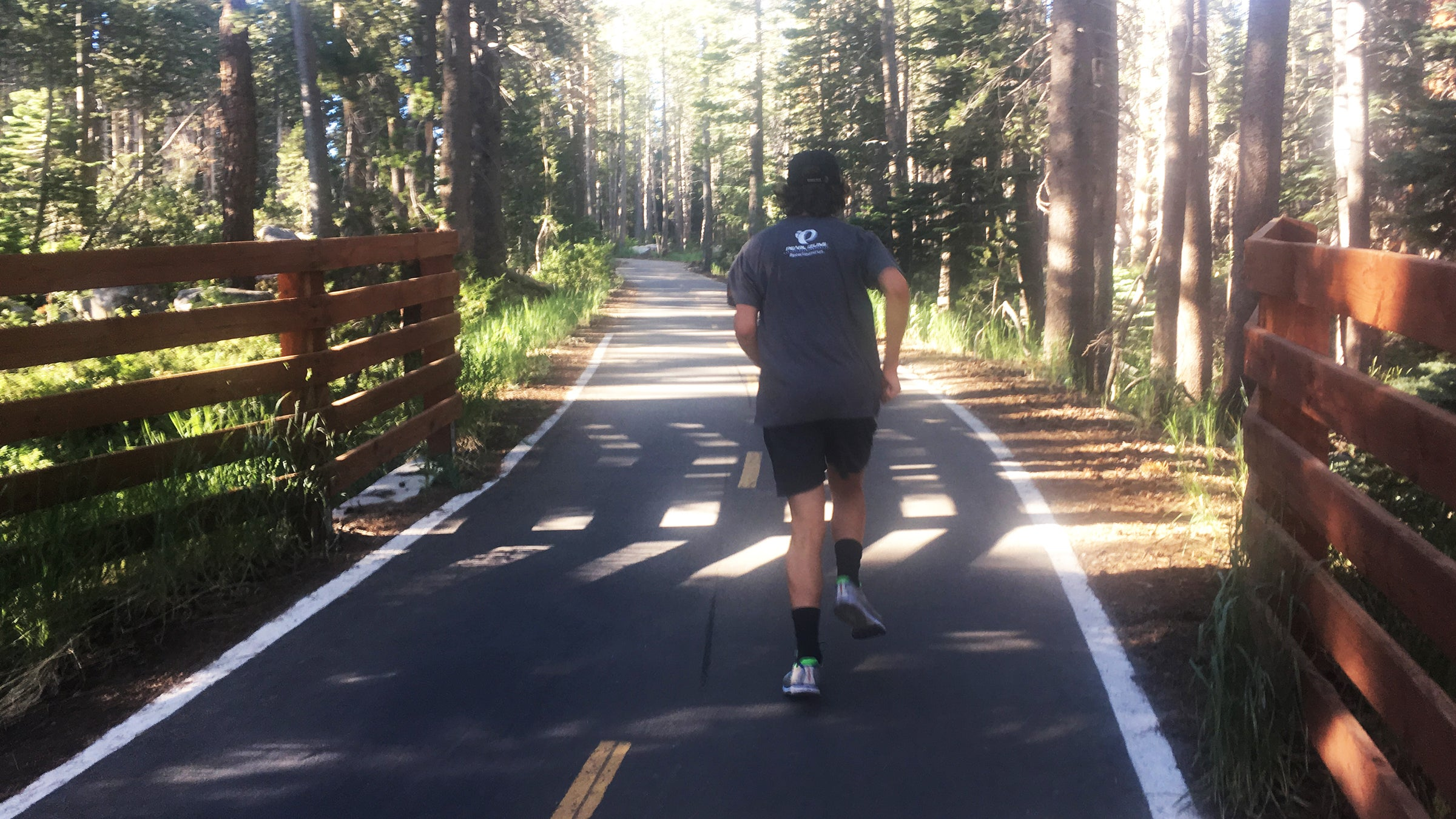 man running on path in forest