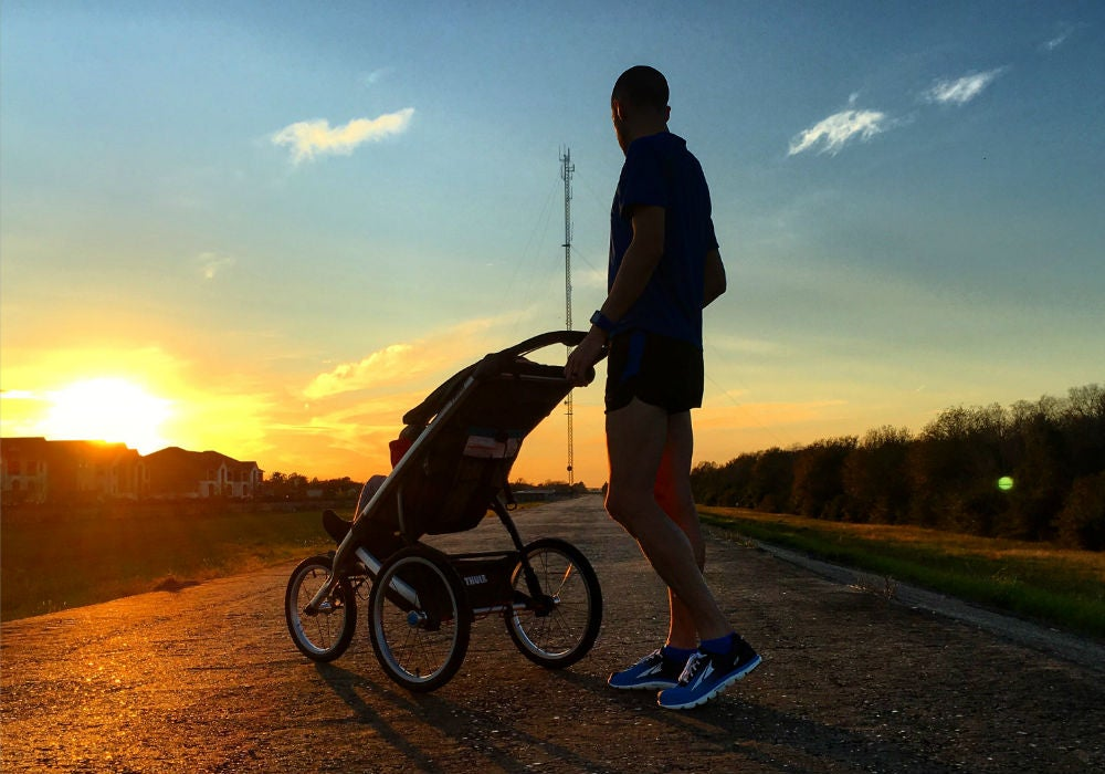 father with running stroller at sunset