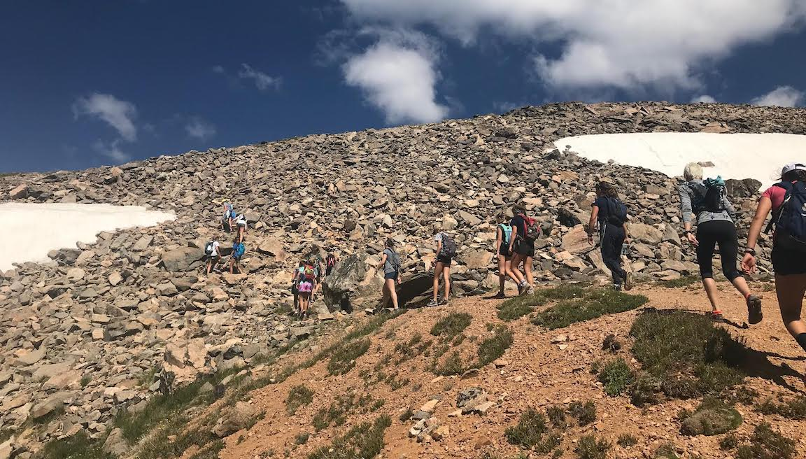 Girls running up rocky mountain.