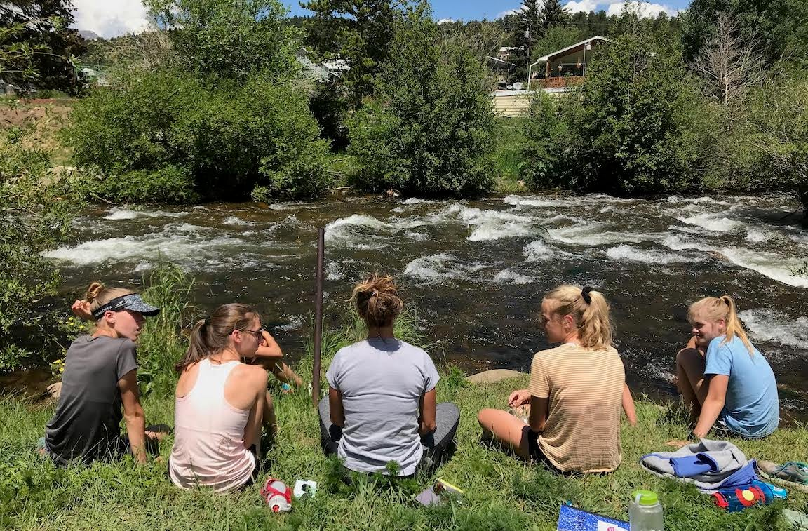 Girls sitting by a stream at a camp.