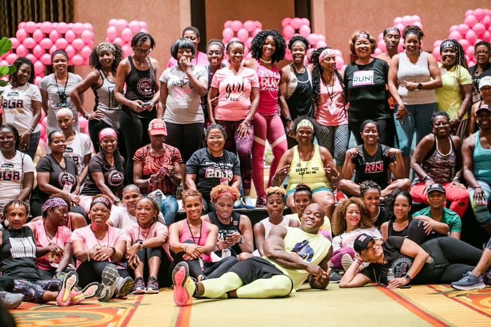 Women from Black Girls RUN pose for an indoor group photo with pink balloons in the background