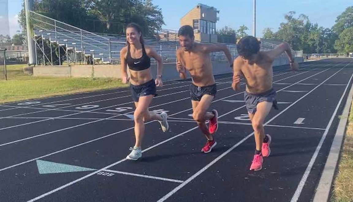 Three smiling runners running off the start line of a track