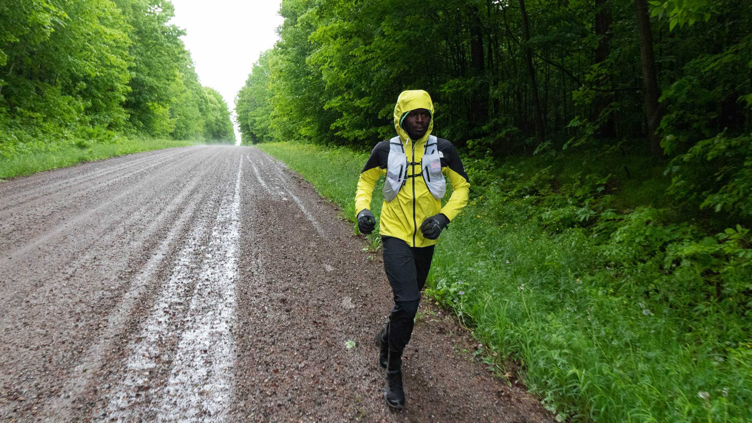 Coree Woltering running on a dirt road in the rain