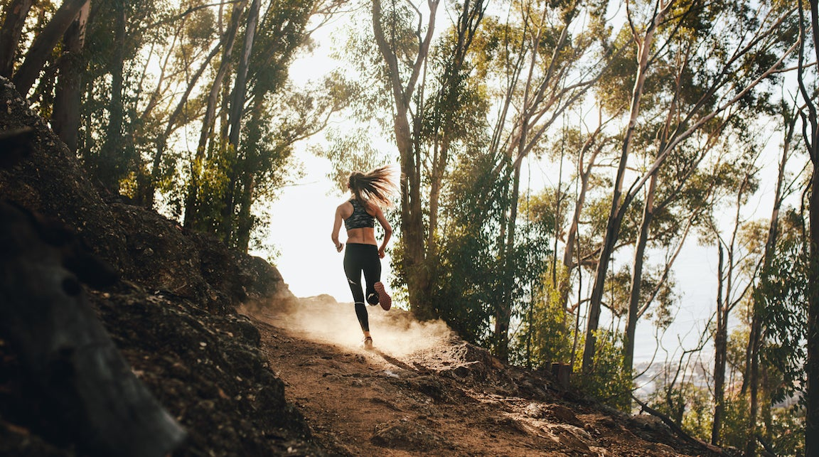 Woman trail running on a mountain path.