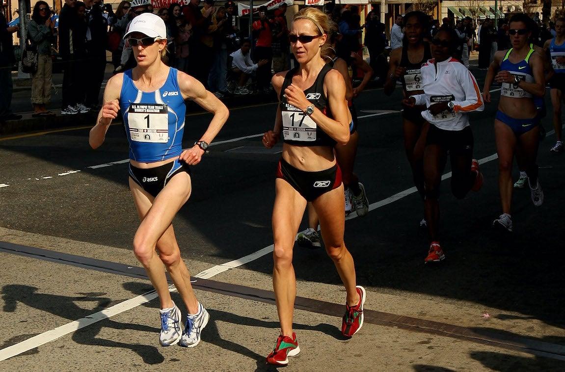 Deena Kastor racing on the road in blue during the U.S. Women's Marathon Trials in Boston.