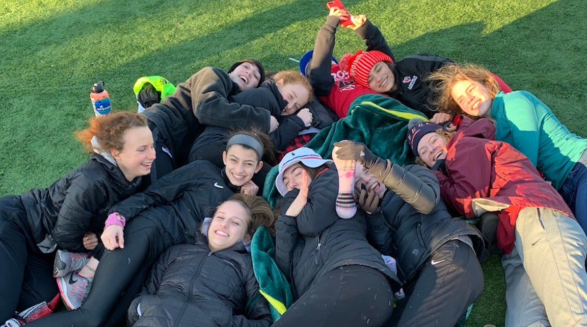 Pile of girls taking a selfie after a track meet.