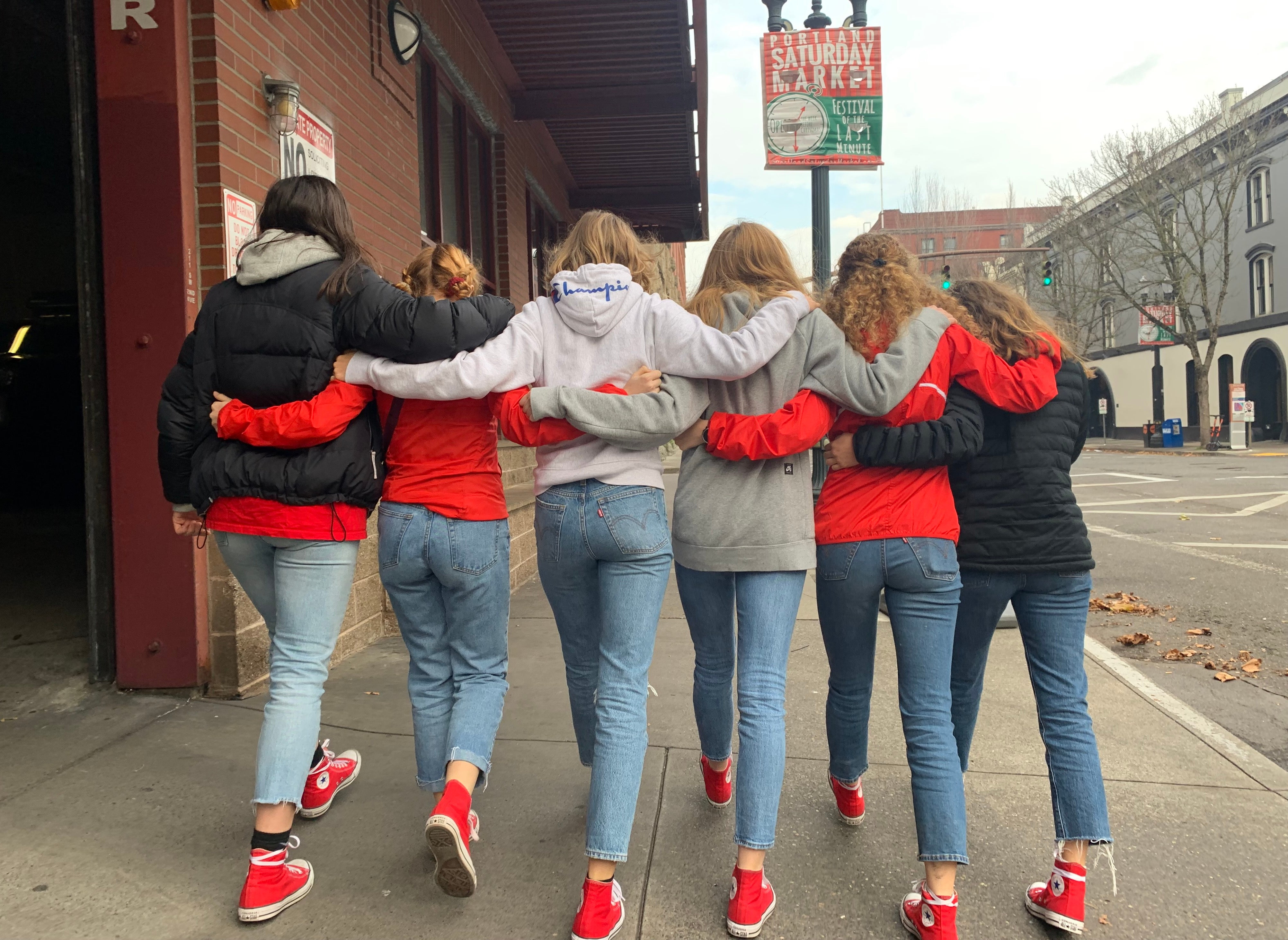 Girls hugging in a line on main street of Oregon town.