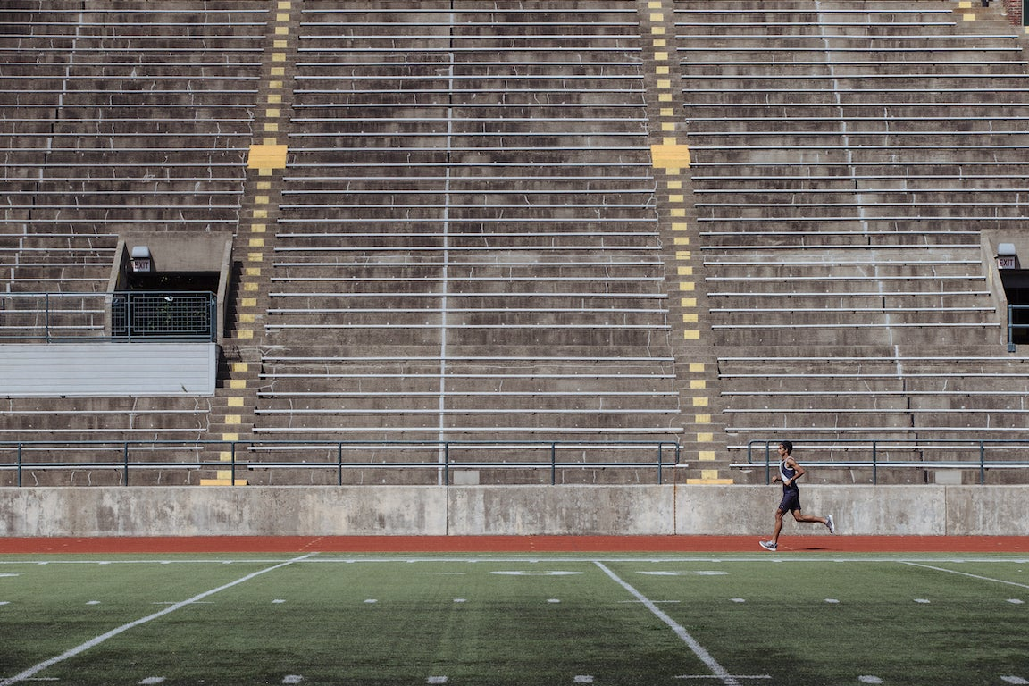 Person running alone on New England track.