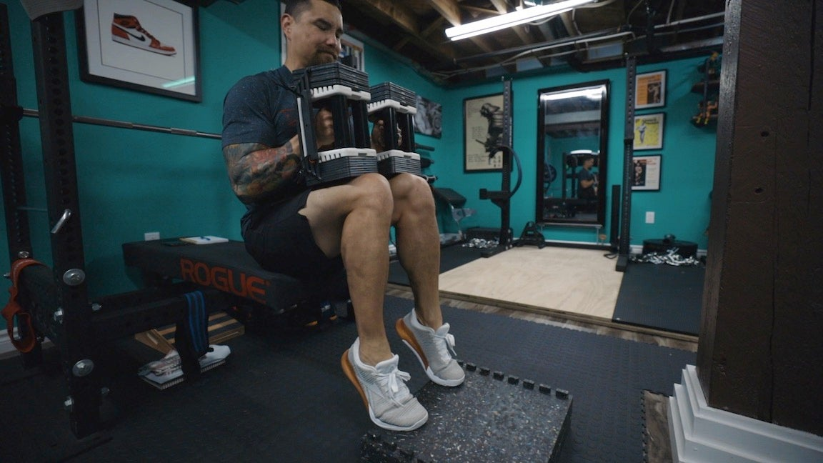 Man doing seated calf raises in gym.