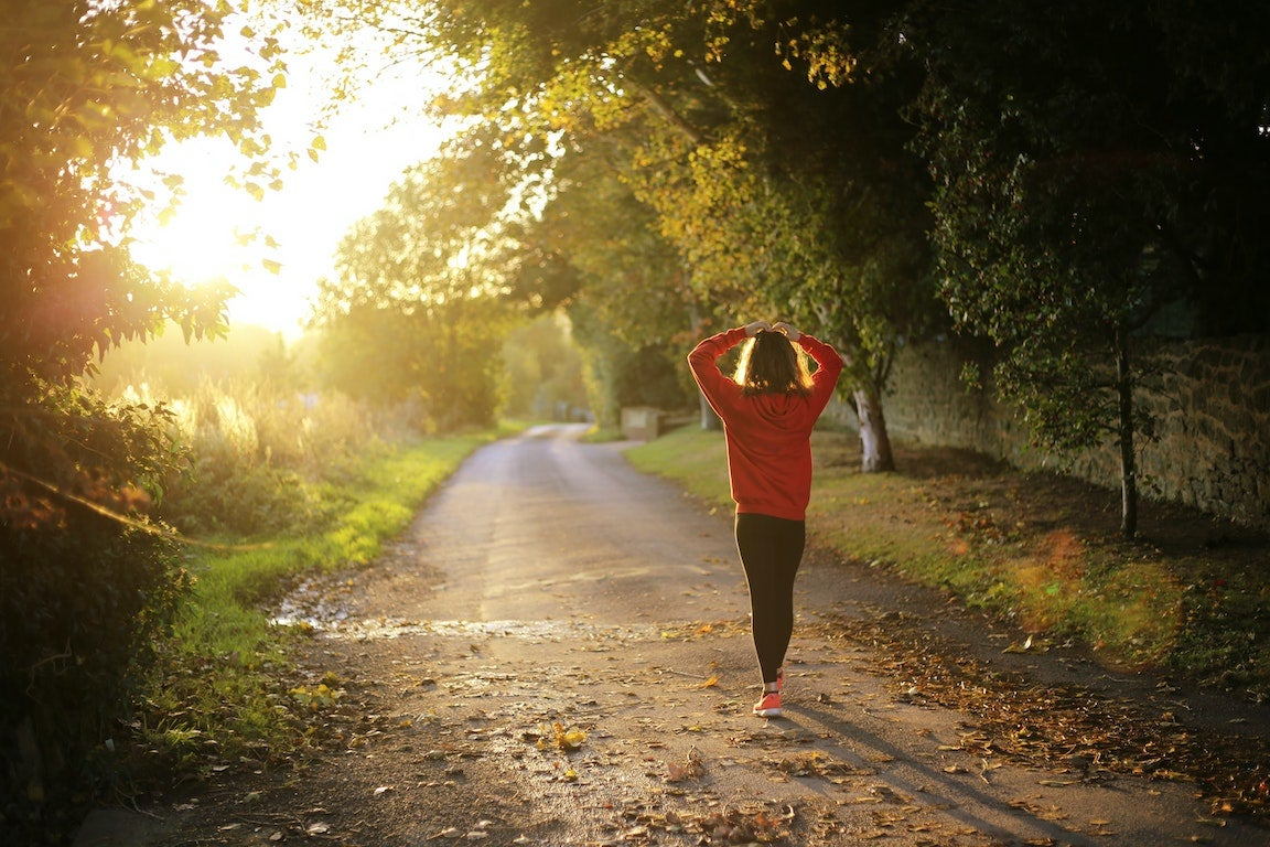 A woman walking after a run with hands on her head.