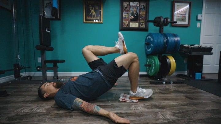 Hombre haciendo taladro de isquiotibiales en el piso del gimnasio.