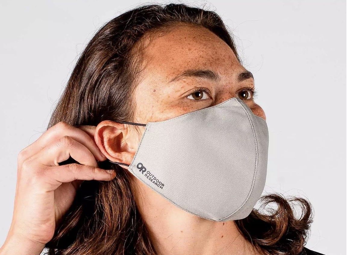 Woman wearing white face mask, securing it behind her ear
