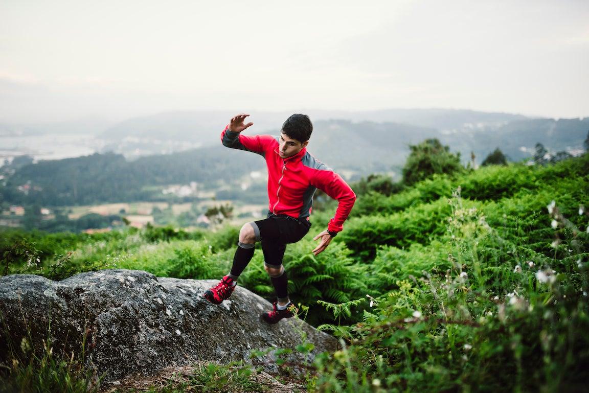 Entrenamiento del hombre del corredor del rastro en la naturaleza, en una roca.