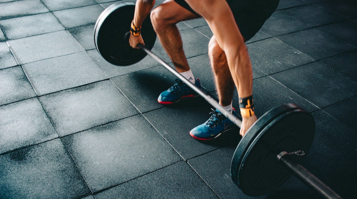 White man lifting bar weights in gym. You just see the bar weight and his arms and legs.