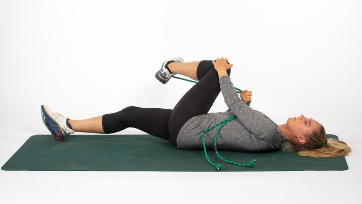 Woman lying on back using rope to stretch gluteals