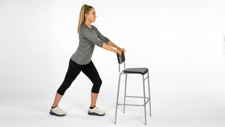 Woman using chair to stretch calves