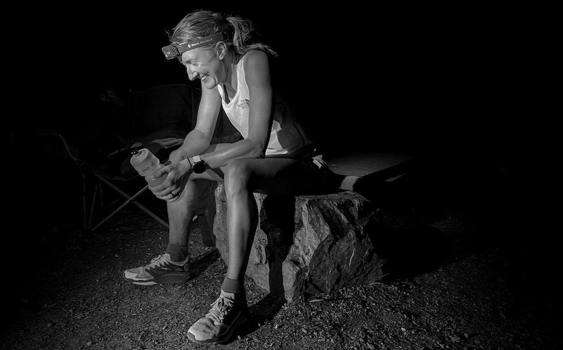 Kaytlyn Gerbin sentada sobre una roca en un sendero con el faro encendido.  Fotografía en blanco y negro.